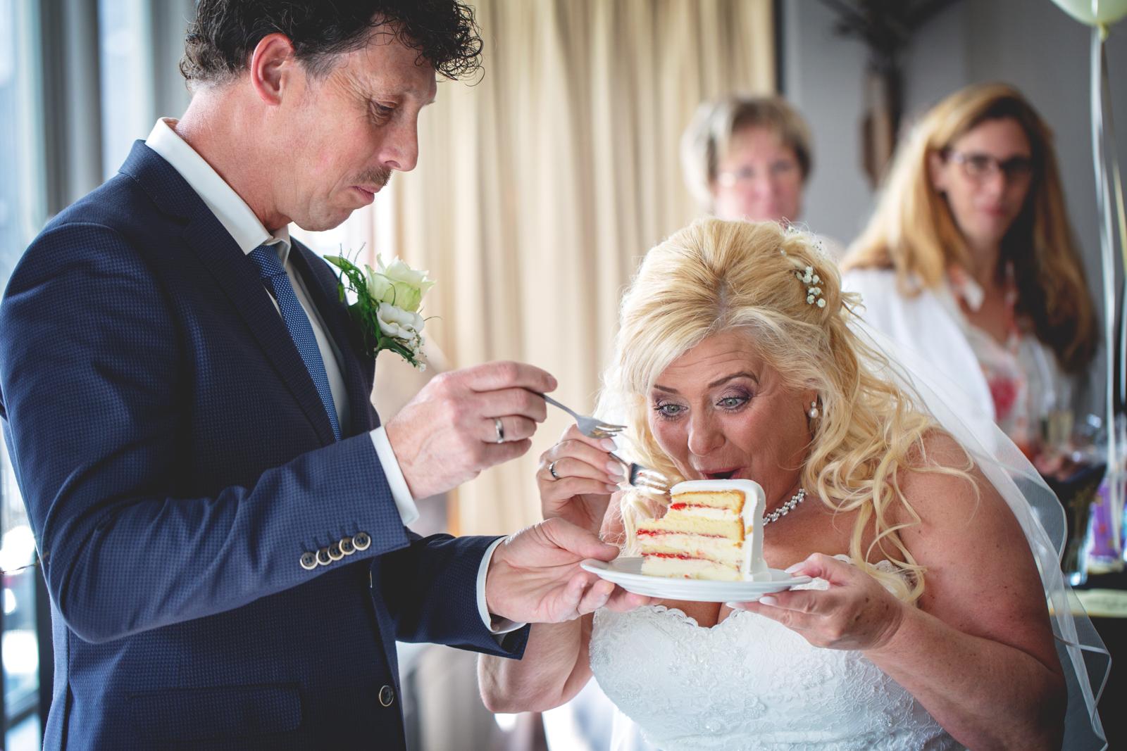 Bruidspaar wat een stuk bruidstaart eet