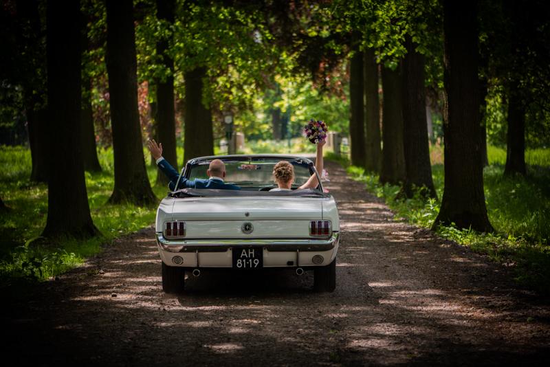 Bruidspaar in een mustang die wegrijden met armen in de lucht