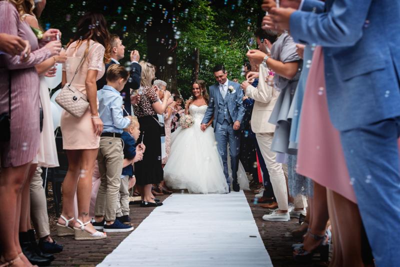 Het bruidspaar wat toegejuicht wordt na de ceremonie met bellenblaas en een haag van mensen