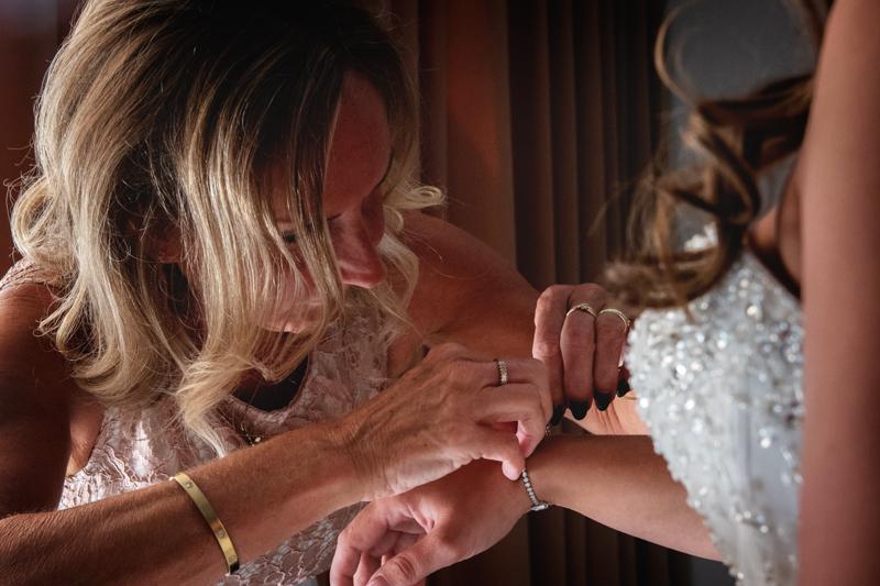 Moeder van de bruid die de armband bij de bruid omdoet
