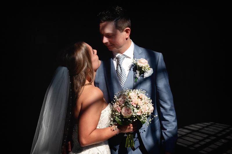 Bruidspaar die elkaar aankijkt waarbij het zonlicht hun in een kader plaatst