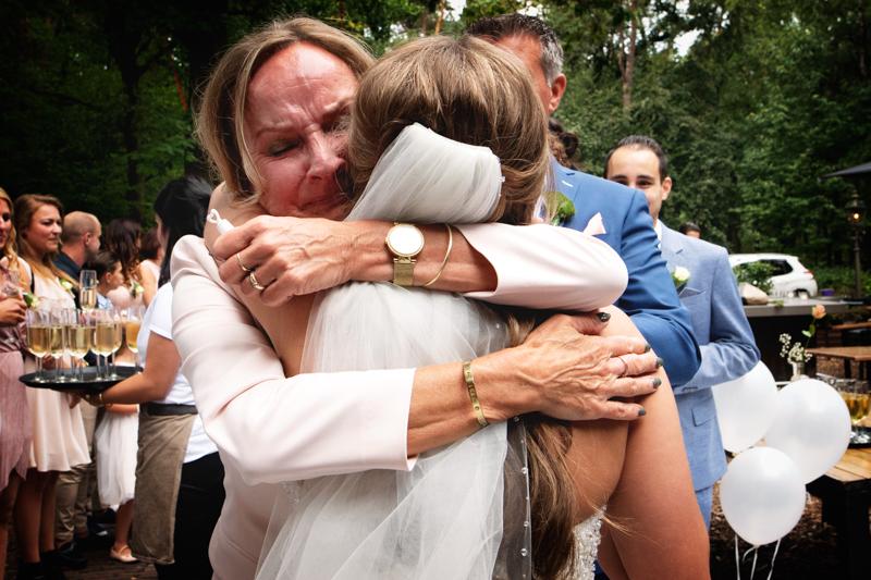 Een emotionele omhelzing van moeder en bruid na de ceremonie