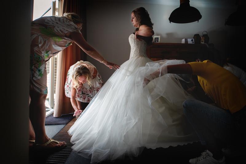 Aankleding bruid door moeder en vriendinnen bij een raam
