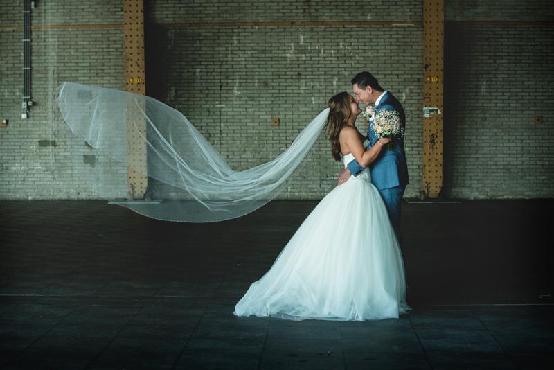 Bruidspaar in een innige omhelzing en een sluier die omhoog waait