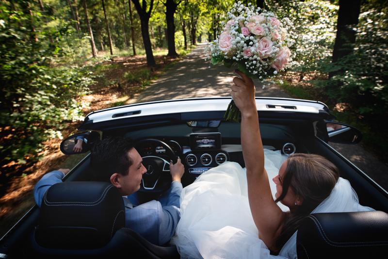 Bruidspaar rijdend in een auto en de bruid die juichend het bruidsboeket omhoog houdt