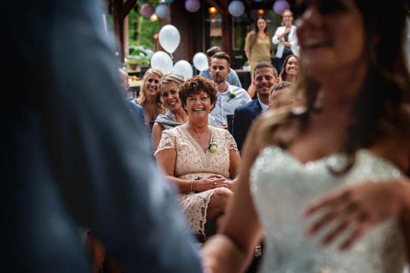 Trotse moeder die naar het bruidspaar kijkt terwijl ze het ja-woord geven