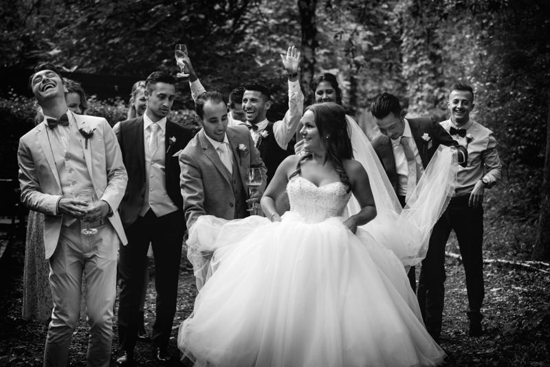 Groepsfoto bruid en vrienden bruidegom die helpen de sleep te dragen