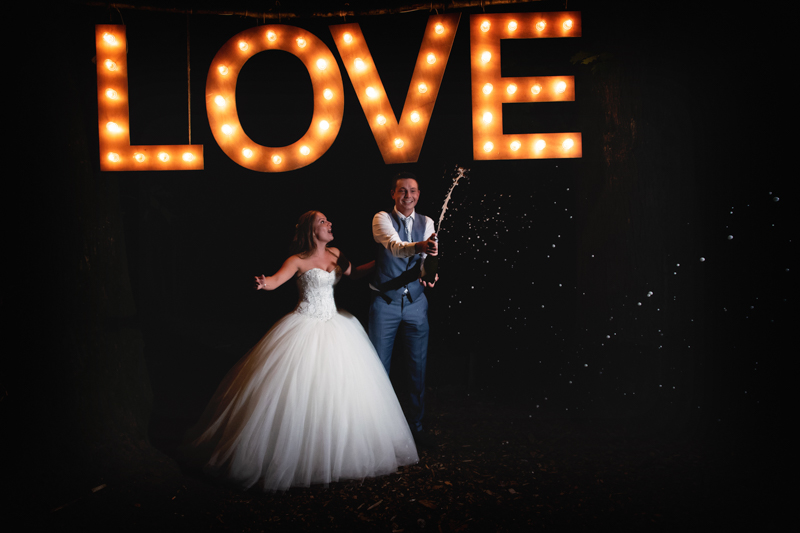 Bruidspaar die champagne spuit na zonsondergang onder een lichtgevend LOVE bord